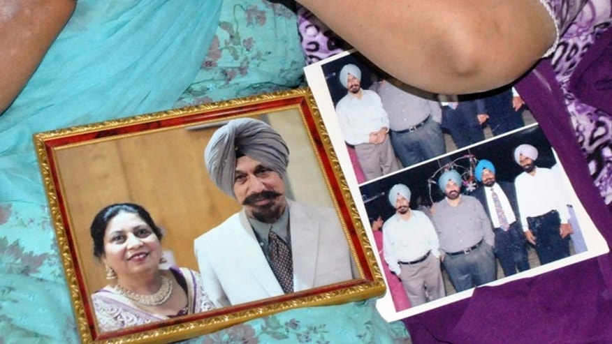 Aug. 6, 2012: Mourning relatives hold a portrait of Satwant Singh Kaleka and his wife, Satpal Kaleka, after the the shooting attack at a Sikh Temple of Wisconsin.