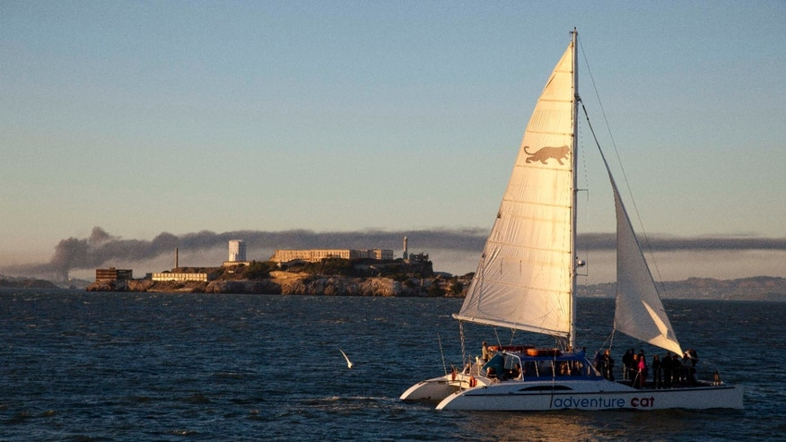 Aug. 6, 2012: Smoke pours from a fire at the Chevron Richmond Refinery, seen at left behind Alcatraz Island as a catamaran sails by in San Francisco.