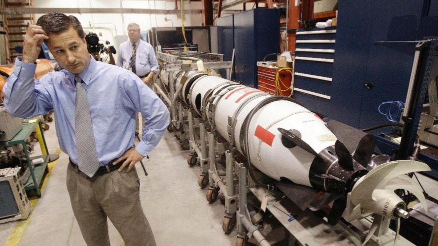 July 31, 2012: Christopher Del Mastro, head of anti submarine warfare mobil targets stands next to an unmanned underwater vehicle (UUV) in a lab at the Naval Undersea War Center in Middletown, RI.