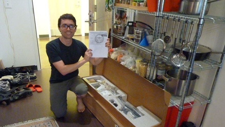 Aug. 7, 2012: This photo, taken in Washington, provided by Seth Horvitz, shows Horvitz, a musician who ordered a 39-inch flat screen television from Amazon, with a military-grade semi-automatic rifle he received in a shipping error.