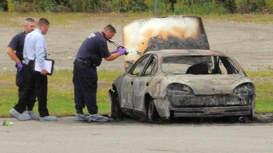 Aug. 13, 2012 - Police investigate a vehicle that burned before dawn Monday,  off Target Industrial Circle in Bangor, Maine.