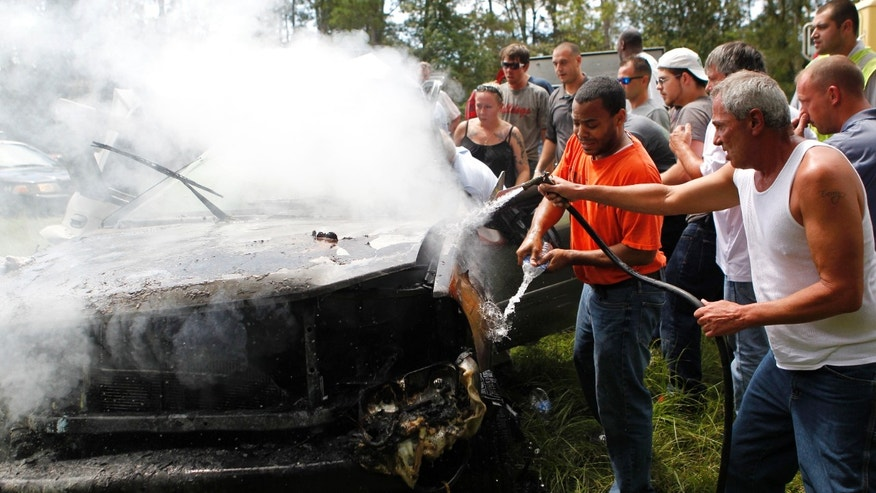 Aug. 16, 2012: Passers-by use a hose from a cement mixer and bottles of spring water to douse the fire as they rescue a woman pinned in a burning car on Interstate 10 in Hancock County, Miss.