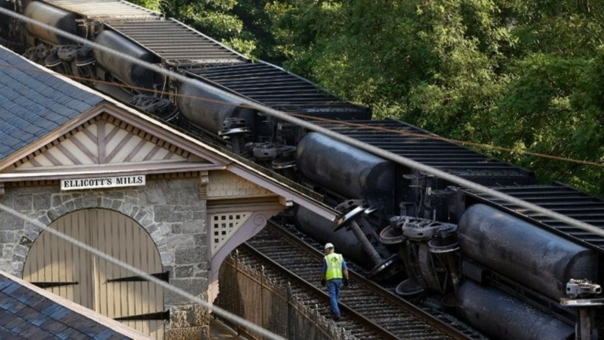 Aug. 21: An official walks alongside part of a CSX freight train that derailed overnight in Ellicott City, Md.