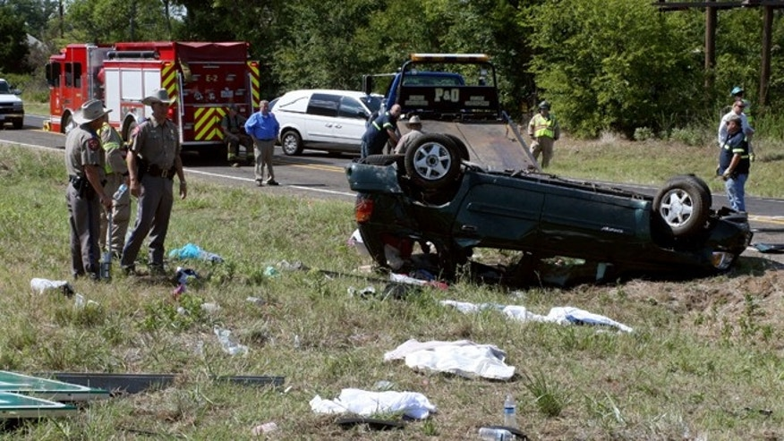 Aug. 20, 2012: Officials work the scene of an accident where a sport utility vehicle taking 10 children to a water park veered out of control and overturned on Interstate 20 near the town of Van, Texas, killing four children and injuring the other nine occupants of the vehicle.