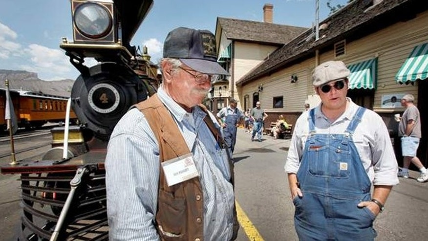 Dan Markoff, left, owner of the Eureka & Palisade woodburning steam locomotive engine, stands with EMT Alex Sharp at the Durango train depot.