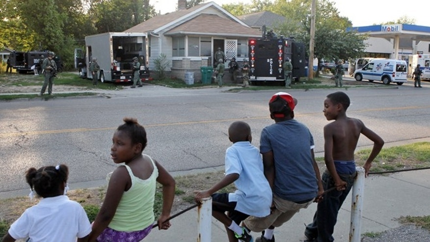 Aug., 23, 2012: Neighborhood children watch as members of the Madison County tactical response team secure a house in Washington Park, Ill., from which a teenage girl escaped after more than two years in captivity.