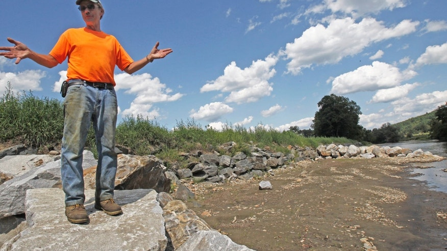 Aug. 22, 2012: Doug Turner stands along the rebuilt river bank of the Mad River at his farm in Waitsfield, Vt.