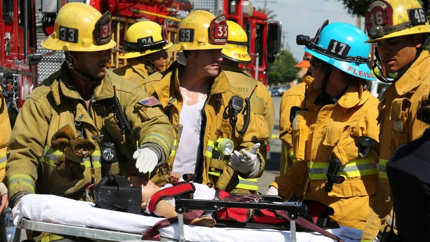 Aug. 29, 2012: Los Angeles City Firefighter paramedics assist a child, one of eight people injured when a car sped onto a sidewalk and plowed into a group of parents and children outside Main Street Elementary school in Los Angeles.