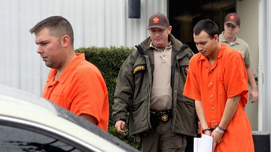 FILE 2011: U.S. Army Sgt. Anthony Peden, 25, left, and Pvt. Isaac Aguigui, 19, are led away in handcuffs after appearing before a magistrate judge at the Long County Sheriffs Office in Ludowici, Ga.