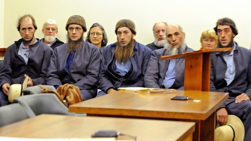 FILE - In this Oct. 19, 2011 file photo, from left, Johnny Mullet, Lester Mullet, Daniel Mullet, Levi Miller and Eli Miller wait to make their pleas in Holmes County Municipal Court in Millersburg, Ohio, in the case involving beard- and hair-cutting attacks against Amish men and women in Ohio.