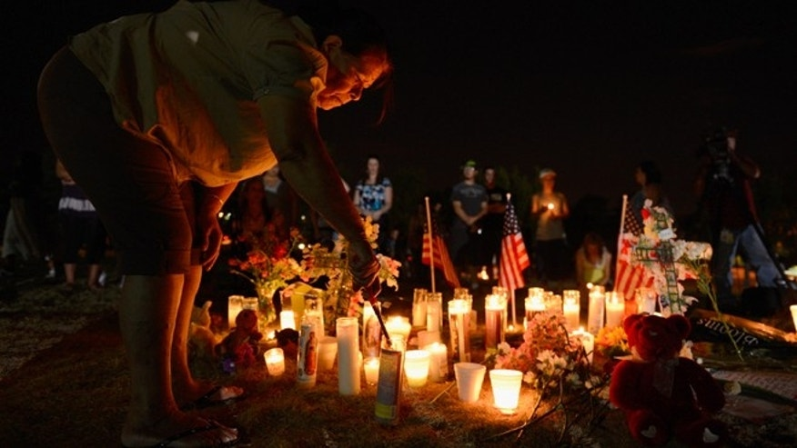JULY 20, 2012 - FILE photo of  woman lighting candles at a makeshift memorial during a vigil for victims of the Century 16 movie theatre where a gunmen attacked movie goers in Aurora, Colorado.
