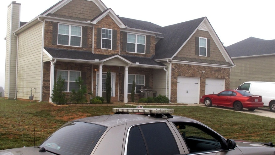 Friday, Sept. 21, 2012 - A Paulding County sheriff's deputy sits outside the suburban home in Dallas, Georgia, near Atlanta, where authorities say Paul and Sheila Comer kept their 18-year-old son in a bedroom for about two years.