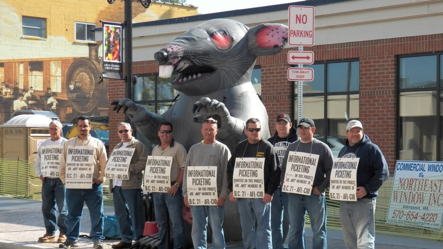 Members of the International Union of Painters and Allied Trades picket in front of the construction site of a new credit union banking location in Pittston, PA that is using non-union labor.
