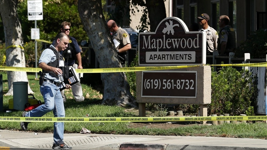 Sept. 25, 2012: A police official walks past the Maplewood Apartments after a shooting in Lakeside, Calif.