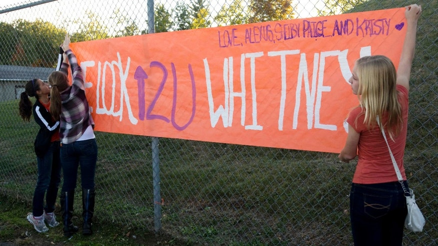 Sept. 28, 2012: From left, Kristy Erway, Hannah Gebnard, and Paige Sharp of Cadillac H.S. hang a banner in support of Whitney Kropps, in West Branch, Mich.