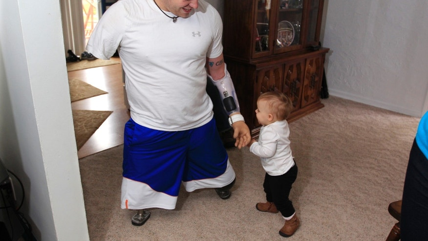 Oct. 4, 2012: Army Staff Sgt. Travis Mills plays with his daughter Chloe in his boyhood home in Vassar, Mich.