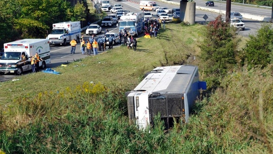 Oct. 6, 2012: Rescue workers and passengers stand by after a bus overturned in a ditch at an exit ramp off Route 80 in Wayne, N.J..