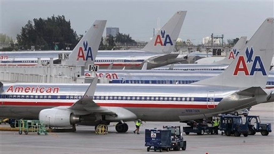 American Airlines jets are parked at the various gates of Miami International Airport on Tuesday, Sept. 18, 2012 in Miami. American Airlines is sending layoff warning notices to more than 11,000 employees although a spokesman says the company expects job losses to be closer to 4,400. The notices went out to mechanics and ground workers whose jobs will be affected as American goes through a bankruptcy restructuring. (AP Photo/The Miami Herald, Carl Juste)  MAGS OUT