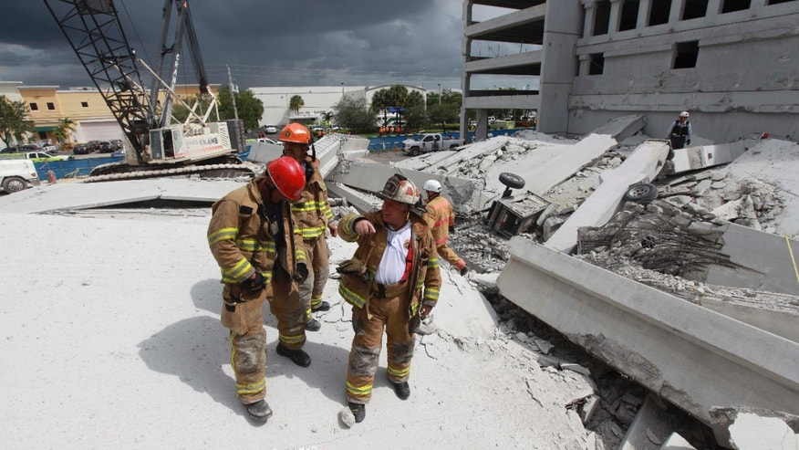 Oct. 10, 2012: Photo provided by Miami-Dade Fire Rescue, firefighters look over the rubble after a section of a parking garage under construction at a Miami-Dade College campus collapsed in Doral, Fla., killing one worker and trapping at least two others in the rubble, officials said.