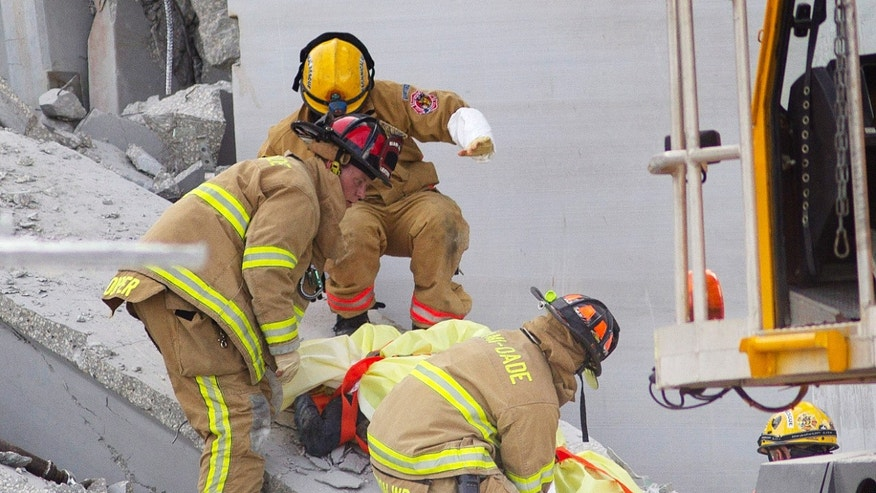 Oct. 10, 2012: Fire Rescue officials work to remove a victim from the collapsed parking garage at the Miami Dade College West campus in Doral, Fla.