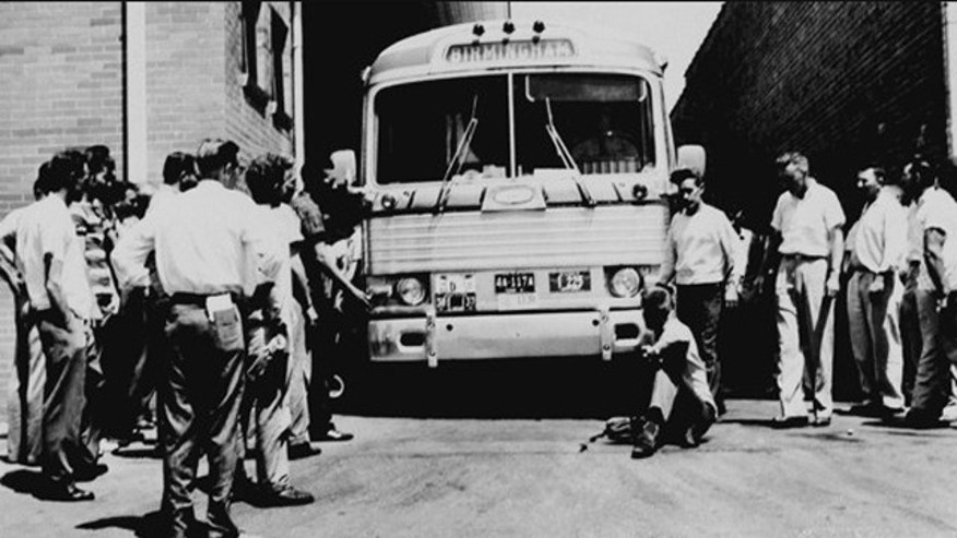 May 14, 1961: An unidentified white man sits in front of a Greyhound bus to prevent it from leaving the station with a load of Freedom Riders testing bus station segregation in Anniston, Ala., as other white men mill around station. The bus was stopped by a flat tire and surrounded by a white crowd outside Anniston, and burned a short time later. The passengers got out without serious injury. (AP)