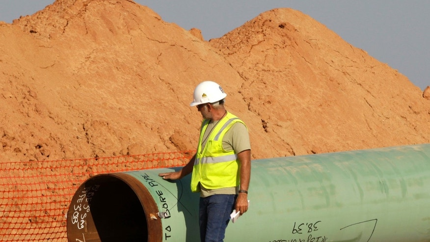 Oct. 4, 2012: A pipeline worker walks the length of a pipe as work continues.
