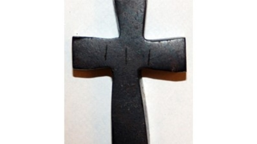 This undated evidence photo provided by the Westminster Police Department shows a wooden cross recovered by police, showing three vertical lines etched into the cross.