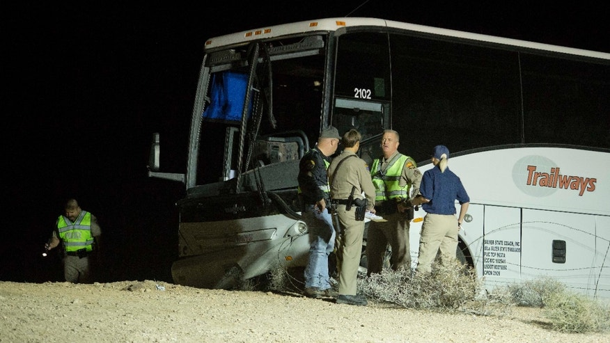 Oct. 19, 2012: Arizona Highway Patrol officers examine the exterior of a tour bus that careened off the highway and crashed off northbound Highway 93.