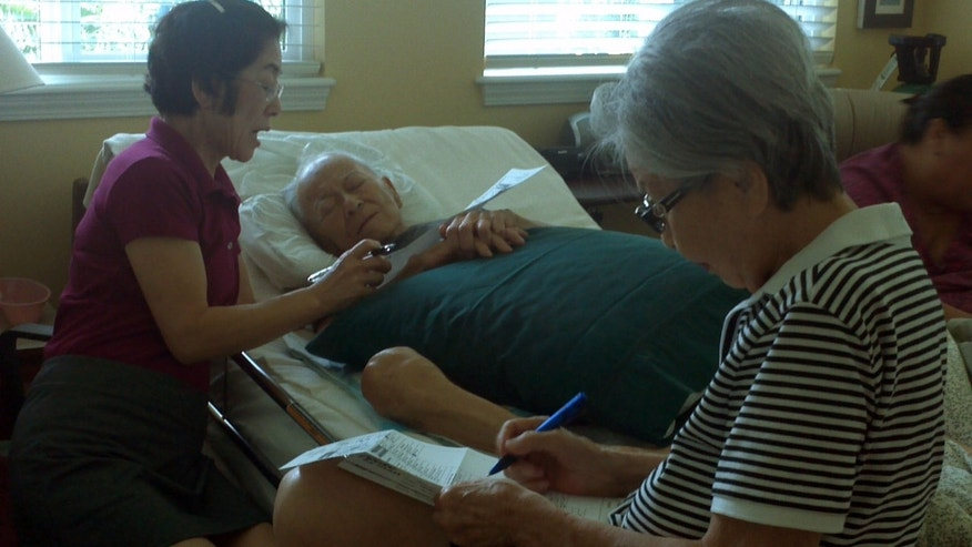 Oct. 17, 2012: Photo provided by Irene Tanabe; Frank Tanabe, center, gets help from his daughter Barbara Tanabe, left, to fill out his absentee ballot in Honolulu while his wife Setsuko Tanabe sits in the foreground.