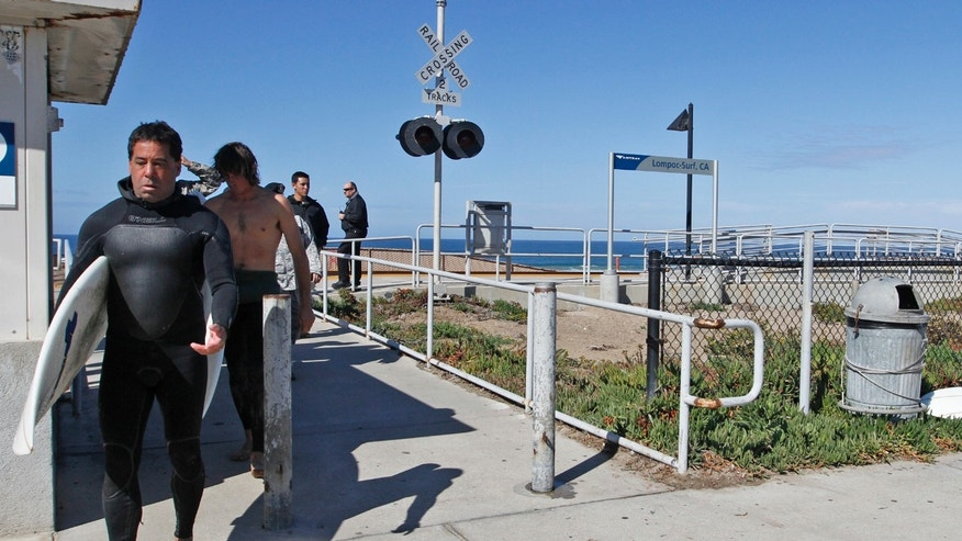 Oct. 23, 2012: Surfers who were surfing with the 38-year-old victim of a fatal shark attack exit Surf Beach in Lompoc, Calif.