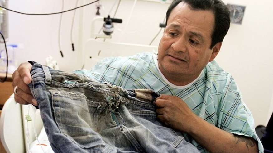 Oct. 23, 2012: Ricky Gilmore, 49, shows the pair of pants he was wearing when he dragged himself four miles down a road for three days last week near Tocito, N.M. after a man and woman he met while he was hitchhiking left him without his wheelchair in Farmington, N.M.