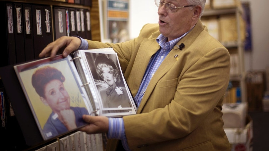 Oct. 19, 2012: Memorabilia collector Ken Kallin shows off autographed photos of Ann B. Davis, left, and Betty Davis, at his Oakland Park, Fla. office. Three decades ago, Kallin began amassing 120,000 pieces in a memorabilia collection that includes photographs signed by Muhammad Ali and Neil Armstrong along with rare books and trading cards.