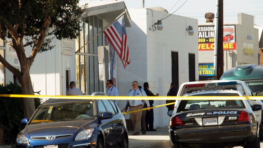 Oct. 24, 2012: Police investigators stand outside a family-owned business, United States Fire Protection Services, in Downey, Calif. Five people were shot and at least two died in shootings at the business and a residence in the Los Angeles suburb Wednesday, according to Downey police Lt. Dean Milligan.