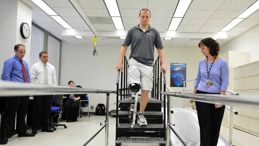 "Oct. 25, 2012: Physical therapist assistant Suzanne Finucane, right, helps Zac Vawter as he practices walking with an experimental ""bionic"" leg."