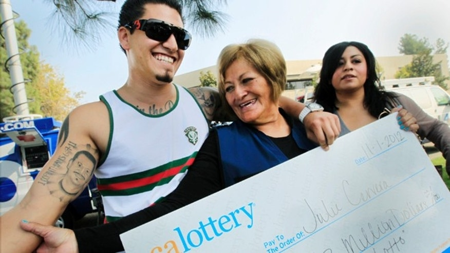 Nov. 2, 2012: Lottery winner Julie Cervera, center, looks at her recently dead son pictured on a tattoo, as she is hugged by her grandson Rudy Ray, left, and daughter Charliena Marquez, right, after a news conference in San Bernardino, Calif.