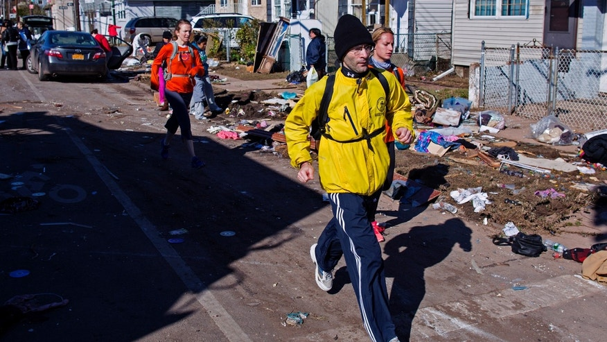 Nov. 4, 2012: Carrying a backpack with goods and supplies, marathon runner Eitan Tabak runs past debris in the hard hit Midland Beach neighborhood of the Staten Island borough of New York. Background right is marathon runner Michelle Mascioli and far left marathon runner Rachel Wheeler of New York.