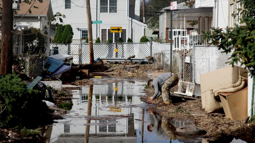 Nov. 2, 2012: A man rinses his hands in flood water while cleaning out a house in a hard-hit neighbor hood in Staten Island, N.Y.