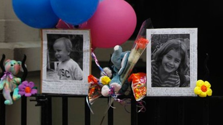 Oct. 27: Photographs of the two children allegedly stabbed by their nanny are displayed alongside balloons and stuffed animals at a memorial outside the apartment building were they lived in New York.