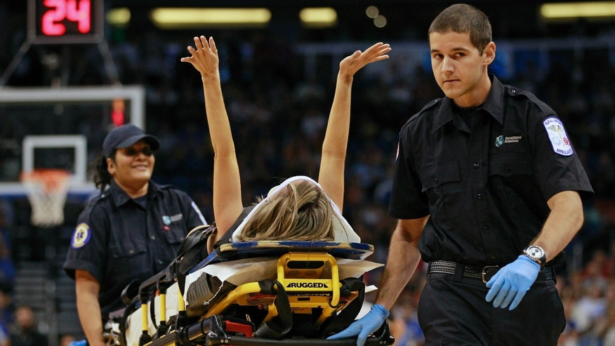 Nov. 13, 2012: Jamie Woode, a former college cheerleader and Magic Stunt Team member, fell during a routine and is wheeled off the floor on a stretcher as she waves her arms to fans during the first half of an NBA basketball game between the Orlando Magic and the New York Knicks in Orlando, Fla.