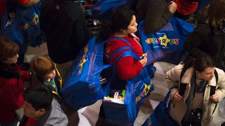 Nov. 22, 2012: A shopper carries bags stuffed with toys in the Times Square Toys-R-Us store after doors were opened in New York.