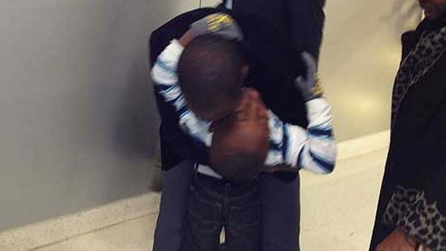 Jabin Bogan embraces his son at Dallas-Fort Worth International Airport.