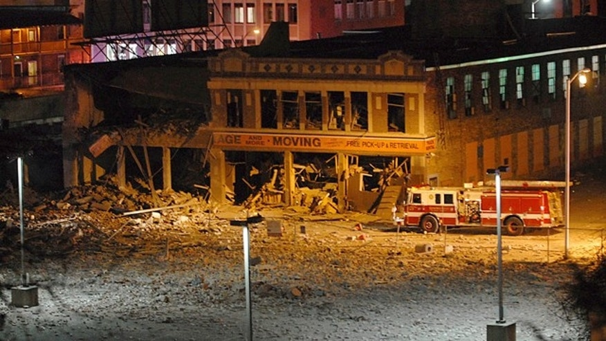 Nov. 23, 2012: A firetruck is parked next to a damaged building after a nearby gas explosion leveled another building in downtown Springfield, Mass.