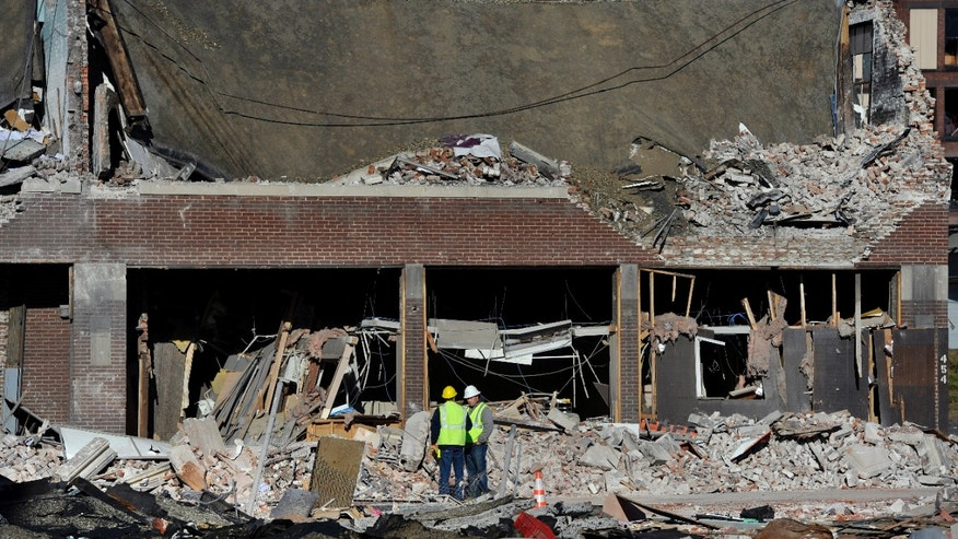 Nov. 24, 2012: Inspectors stand in debris, at the site of a gas explosion that leveled a strip club in Springfield, Mass., on Friday evening. Investigators were trying to figure out what caused the blast where the multistory brick building housing Scores Gentleman's Club once stood.