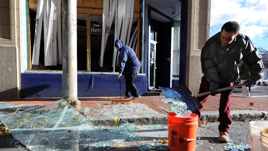 Nov. 24, 2012: Robert Spano, left, and Alan Hugley clean up broken glass, outside of Punta cana Restaurant & Bar, a few blocks from the site of a Friday-evening gas explosion that leveled a strip club in Springfield, Mass.