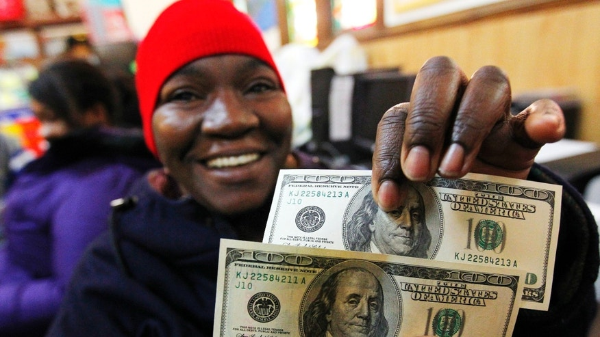 Nov. 29, 2012: Charlotte Muhammad holds up two $100 dollar bills she got from Secret Santa, at St. Joseph's Social Service Center in Elizabeth, N.J.