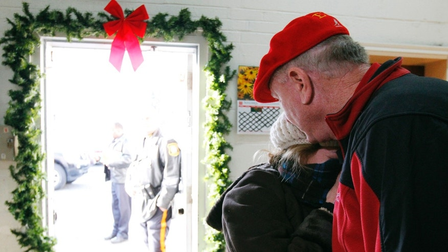 Nov. 29, 2012: A woman hugs Secret Santa after receiving a $100 dollar bill from the wealthy philanthropist from Kansas City, Mo. Secret Santa distributed $100 dollar bills to needy people at St. Joseph's Social Service Center and other locations in Elizabeth, N.J.