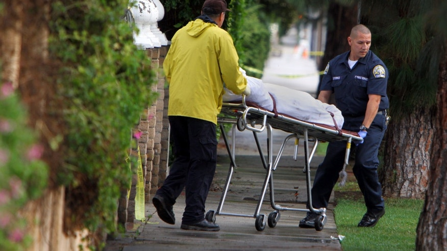 Dec. 2, 2012: A covered body is removed from the scene on a gurney after police responded to a report of a shooting and found the bodies of four people outside a boarding house in Northridge, Calif.