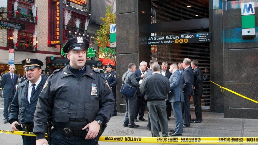 Dec. 3, 2012: Uniformed and plainclothes police officers stand outside a New York subway station after a man was killed after falling into the path of a train. Transit officials say police are investigating whether he could have been pushed onto the tracks.