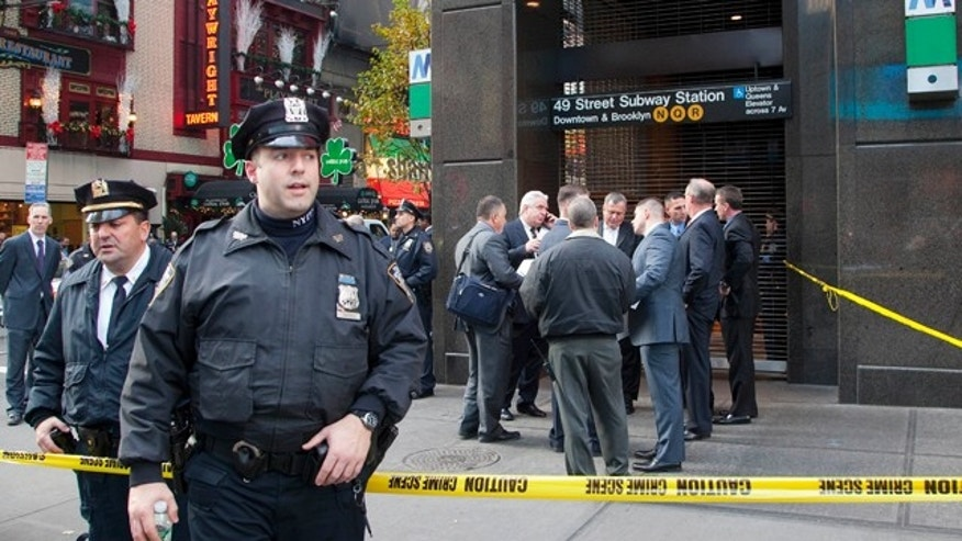 Dec. 3, 2012: Uniformed and plainclothes police officers stand outside a New York subway station after a man was killed after falling into the path of a train.
