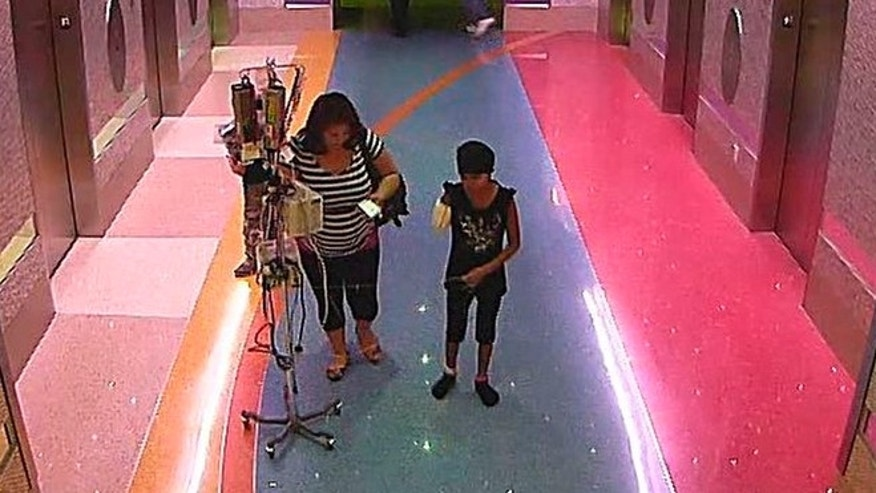 Dec. 3: In this hospital surveillance photo released by the Phoenix Police Department, a woman is seen with her 11-year-old daughter, a leukemia patient who had her arm amputated and a heart catheter inserted due to an infection.